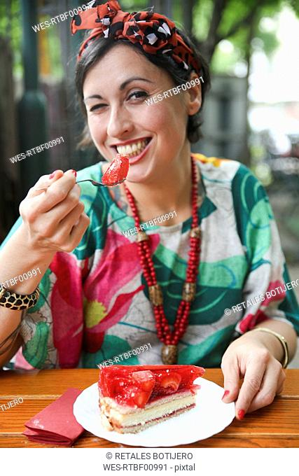 Woman eating strawberry cake in street cafe