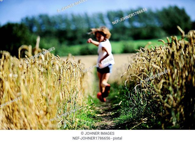 Girl running through wheat field