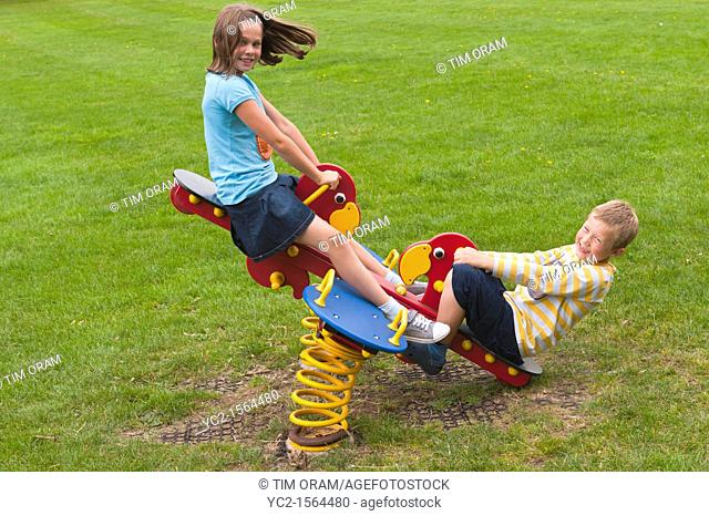 A girl and boy  10 and 8  play on a seesaw in a Uk park playground