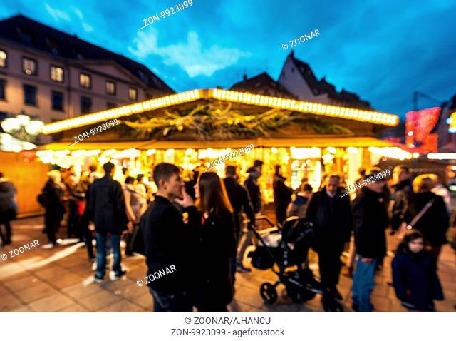 Defocused view of Christmas Market holiday shopping season with silhouettes of people and children's admiring Christmas stall chalet