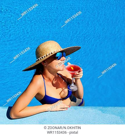 Woman at poolside with cosmopolitan cocktail