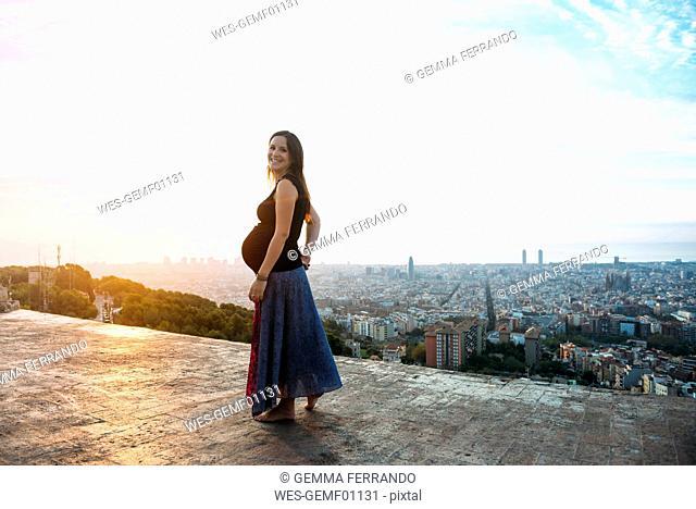 Spain, Barcelona, Pregnant woman enjoying view over city