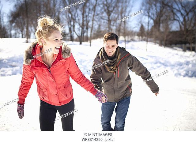 Caucasian couple ice skating on frozen lake