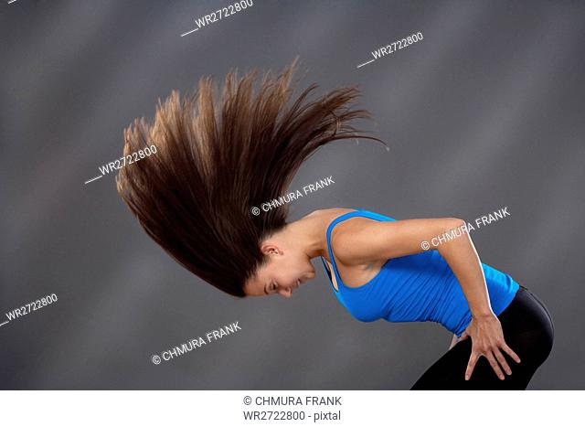 woman with long brown hair shaking her head to make it fly