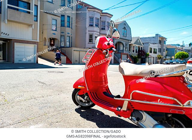 A bright red Vespa scooter parked on the street on a sunny day in the Cow Hollow neighborhood of San Francisco, California, August 28, 2016