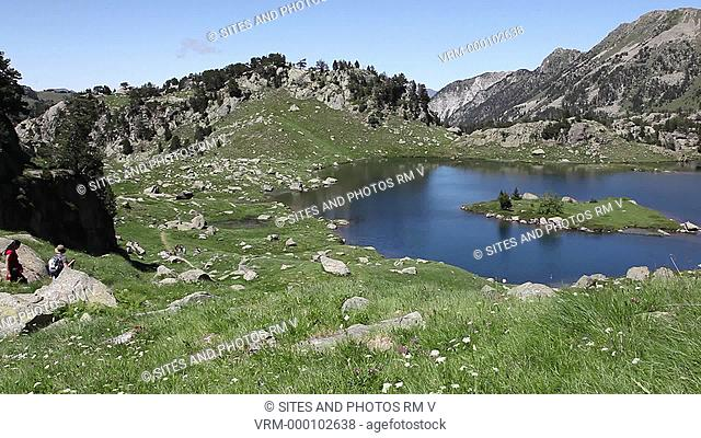 Exterior, LS, Locked Down Shot, Daylight, view of the Pyrenees Mountains. Seen are trackers descending towards a lake with a small island in it