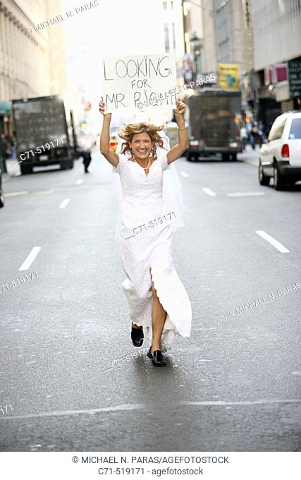 Bride in wedding dress running down street holding a sign overhead reading 'Looking for Mr. Right'