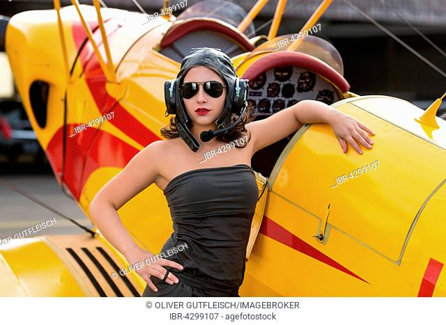 Young woman in green jumpsuit and old flying cap poses with yellow biplane, Fashion