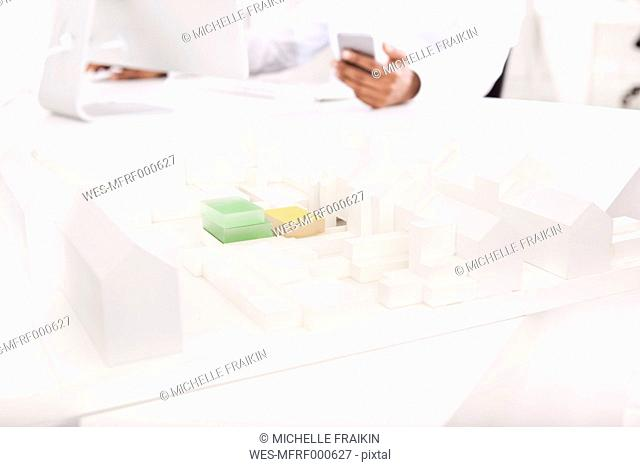 Architectural model on desk with working man in the background