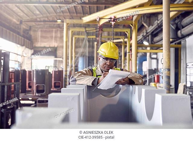 Steelworker with clipboard in steel mill