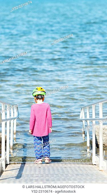 Little girl wearing helmet standing on ramp by water hesitating and contemplating