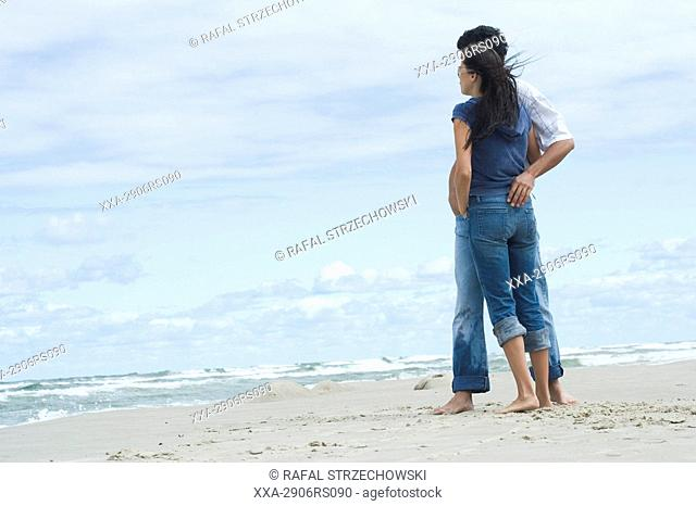 couple embarcing on beach