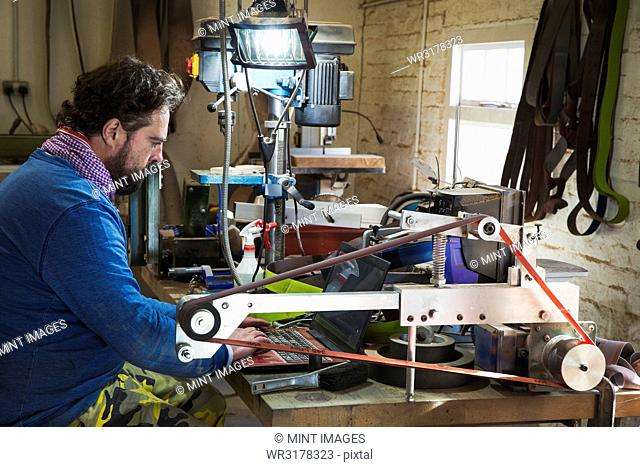 A craftsman sitting at table in a workshop, using laptop computer, typing among the cluttered on the workbench