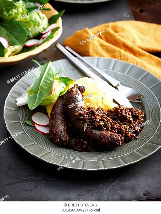 Meal with roast Italian sausages with mashed potato and lentils