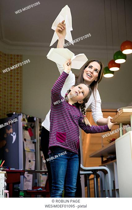 Happy mother and daughter throwing paper plane together at home