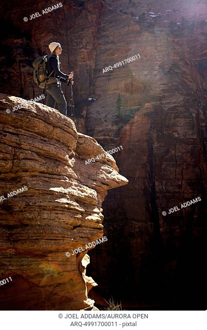 A young woman in a hat and sunglasses hikes the red rock of Zion National Park