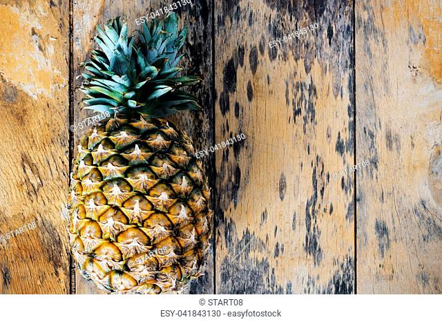 Yellow pineapple on the old wooden floor