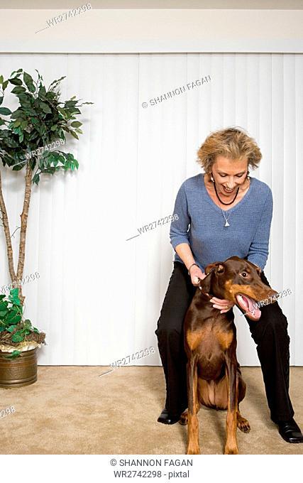 Senior woman with pet Doberman