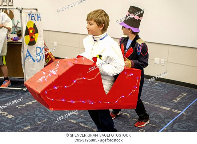 """Laguna Beach, CA, middle school boys ride a cardboard vehicle while demonstrating """"""""Unlikely Attraction,"""""""" their science project involving an amusement park..."""