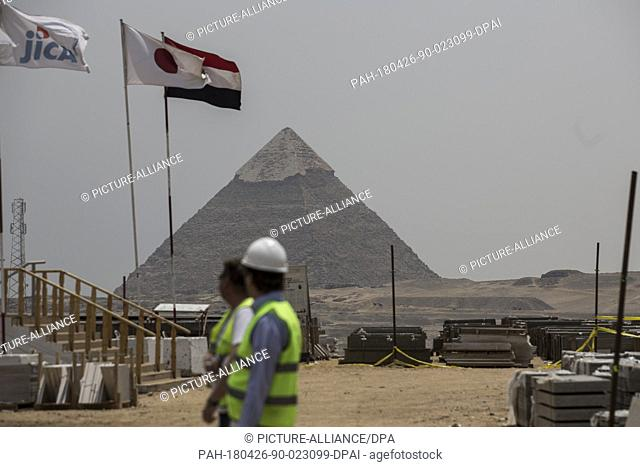 Construction workers walk at the construction site of the Grand Egyptian Museum, backdropped by the Great Pyramid of Khufu, in Giza, Egypt, 26 April 2018