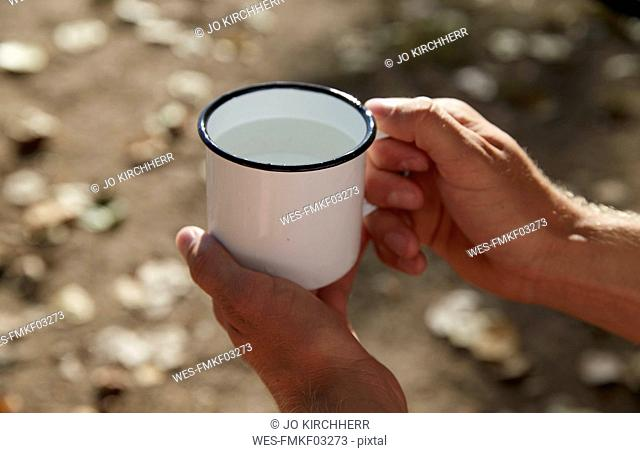 Hands holding enamel mug with water