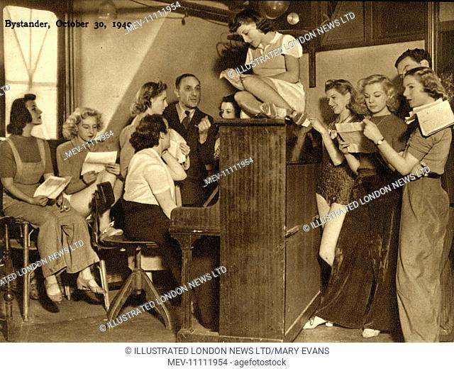 Eric Woodburn, seated at the piano, rehearses along with the girls of the Revudeville company at the Windmill Theatre, London
