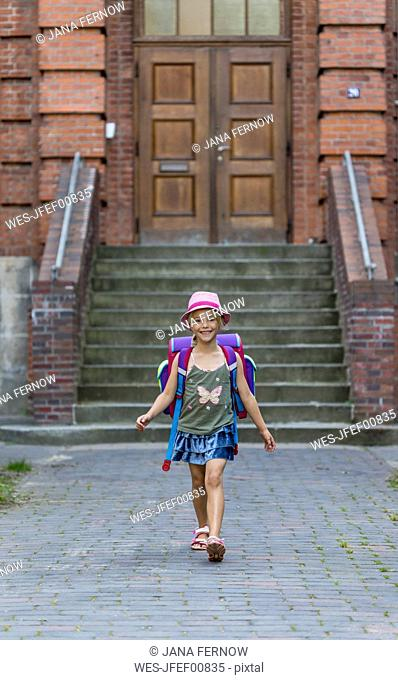 Smiling little girl with school bag in front of her school