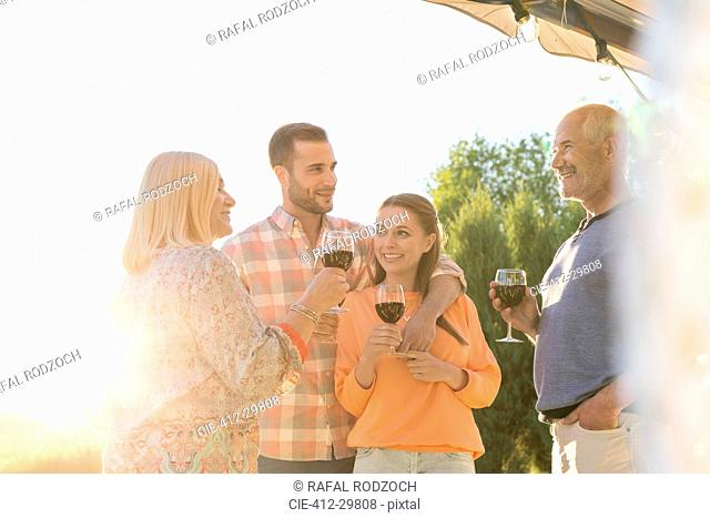 Family talking and drinking wine on sunny patio