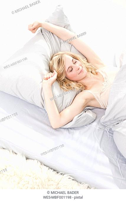 Germany, Leipzig, Young woman stretching in bed