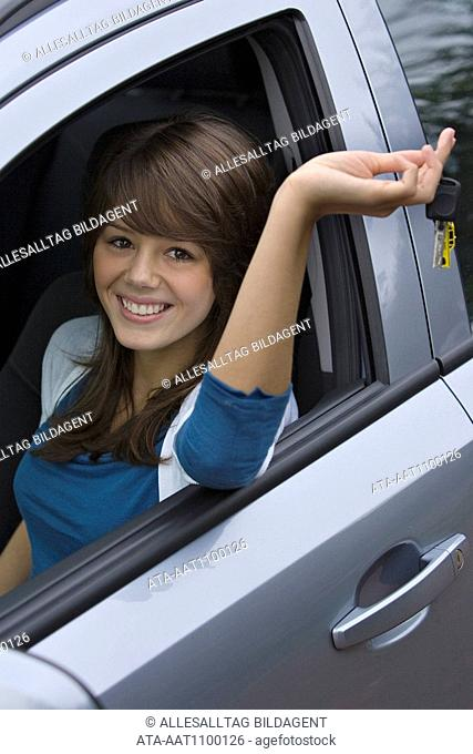 Young female driver presenting her car key