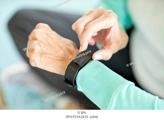 Senior woman using fitness tracker on wrist