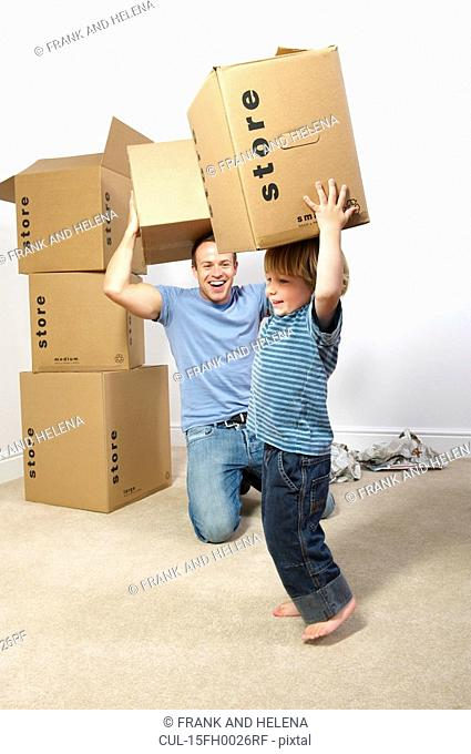 Father and son playing with moving boxes