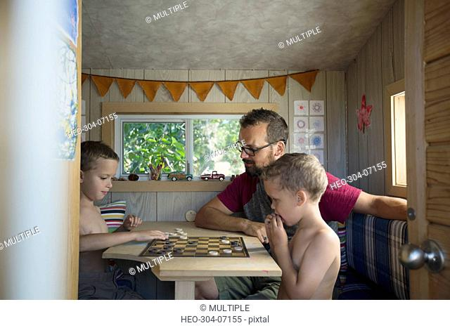 Father and sons playing checkers at table in treehouse