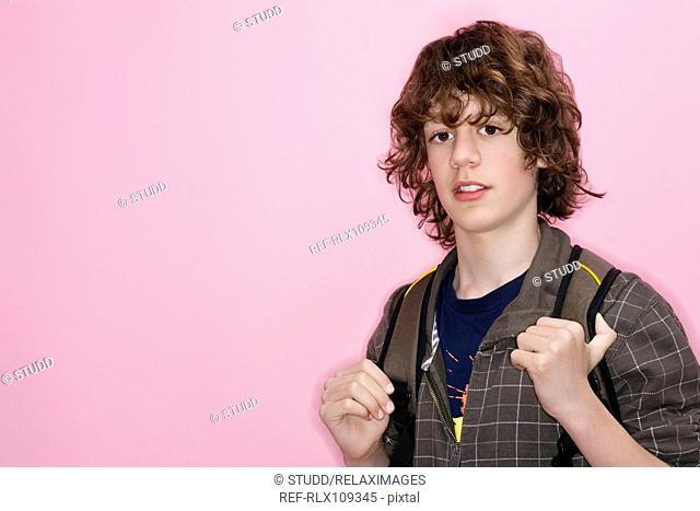 Portrait of teenage boy 14-15 against pink background, Munich, Germany