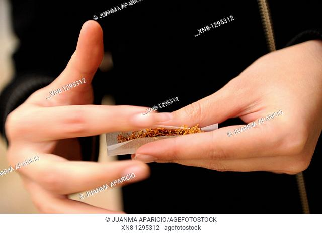 Young woman rolling a joint