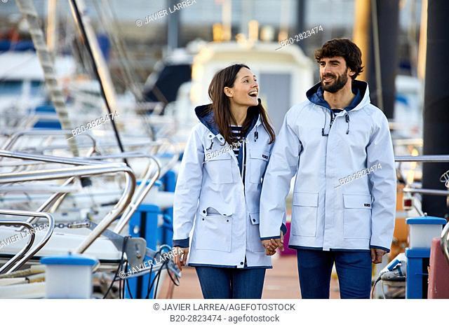 Couple with raincoat, Port of Getaria, Gipuzkoa, Basque Country, Spain, Europe