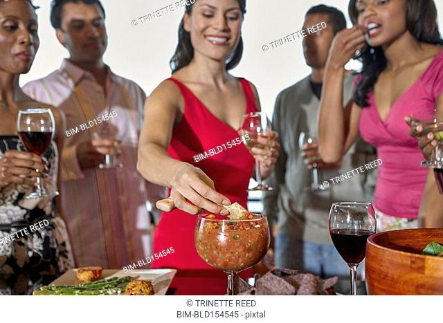 Woman eating chips and salsa at party