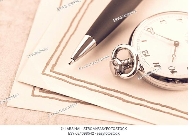Letter paper, vintage pocket watch and pen. Concept of writing, correspondence and old fashioned communication