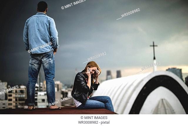 A woman sitting and talking on a mobile phone on a city rooftop, with a man standing behind her