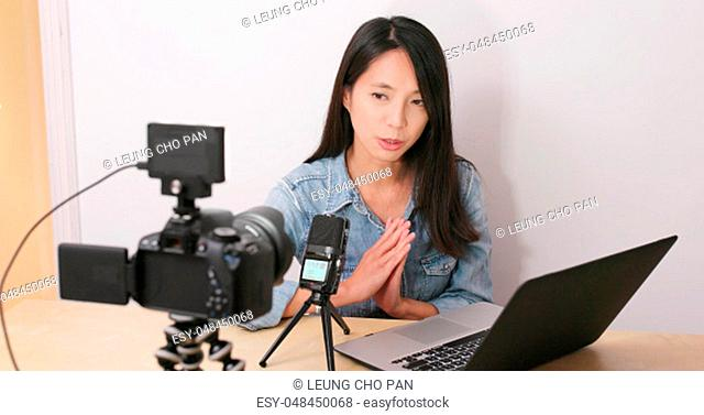 Woman talking in front of the digital camera with her notebook computer for making vlog at home