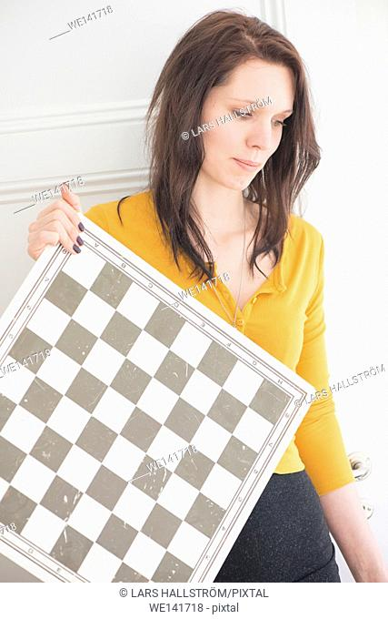 Serious woman holding chessboard in home interior. Concept of strategy, leisure activity and contemplation