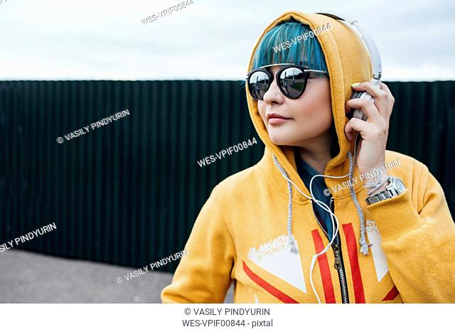 Portrait of young woman with dyed blue hair listening music with headphones