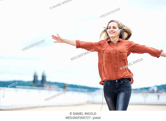 Happy woman with arms outstretched listening music with headphones
