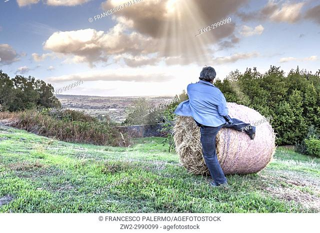 Front view of man who trains with a bale of hay at field against dramatic sky. Bonacardo, Sardinia. italy