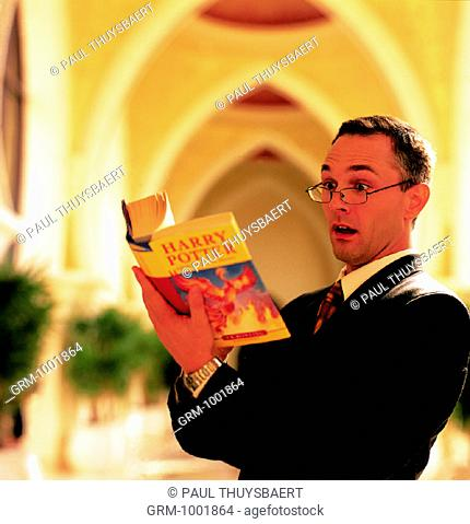 Adult man reading a Harry Potter book