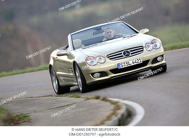 Mercedes SL 500, model year 2005-, gold, driving, diagonal from the front, frontal view, country road, open top