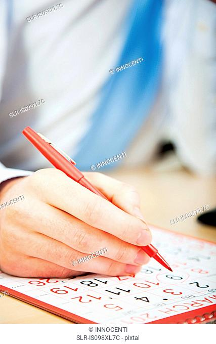 Office worker marking calendar with red pen