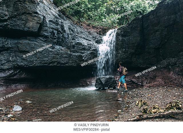 Russia, Far East, Khasanskiy, man hiking at a waterfall
