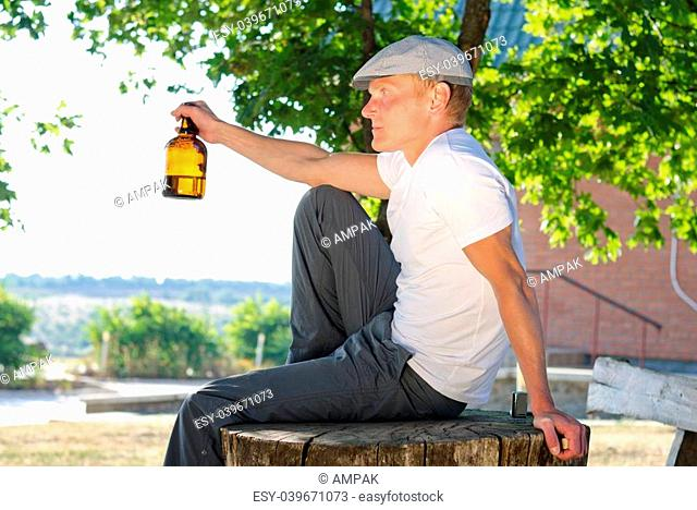 Man sitting outdoors on an old tree stump enjoying a drink holding a brown bottle of alcohol or spirits in his hand