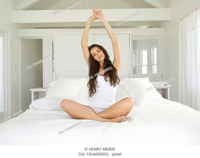 Female stretching on bed